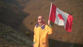 Um homem nas montanhas est? e guarda a bandeira canadense Est? vestindo a roupa e vidros amarelos brilhantes filme
