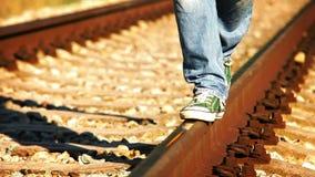 Um homem nas sapatilhas verdes e em calças de brim luz-azuis anda ao longo do trilho filme