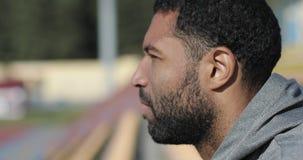Um homem negro com uma barba e um fato de esporte senta-se em um estádio na queda video estoque