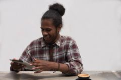 Um homem negro novo que trabalha e que estuda mantendo o portátil e a pena que fazem trabalhos de casa imagem de stock