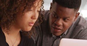 Um homem negro novo recomenda uma mulher afro-americano ao trabalhar em um escritório contemporâneo fotos de stock
