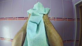 Um homem no banheiro limpa sua cara com uma toalha da lo??o p?s barba filme