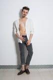 Um homem no calças de brim cinzentas e casaco de lã branco Imagem de Stock