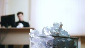 Um homem no escritório que escreve algo, amarrota o papel e joga-o direito no lixo video estoque