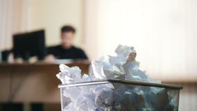 Um homem no escritório que escreve algo, amarrota o papel e joga-o no lixo filme