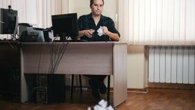 Um homem no escritório que escreve algo e o papel dos lances no lixo vídeos de arquivo