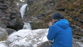 Um homem no sportswear está descansando pela cachoeira Bebe o chá quente de uma caneca video estoque