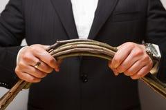 Um homem no terno esforça-se para quebrar um grupo de ramos Imagens de Stock Royalty Free