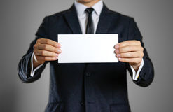Um homem no terno preto que guarda o branco claro vazio da folha clos Fotos de Stock Royalty Free