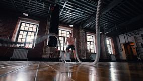 Um homem no treinamento no gym Treinando suas mãos com batida das cordas video estoque