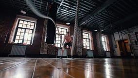 Um homem no treinamento no gym Treinando suas m?os com as cordas que batem no assoalho filme