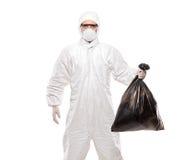 Um homem no uniforme que prende um saco de lixo preto Fotografia de Stock