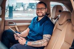 Um homem nos monóculos com tatuagem em seu braço usando o PC portátil da tabuleta em um banco traseiro de um carro Imagens de Stock Royalty Free