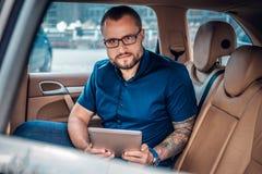 Um homem nos monóculos com tatuagem em seu braço usando o PC portátil da tabuleta em um banco traseiro de um carro Fotografia de Stock