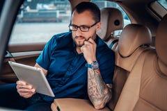 Um homem nos monóculos com tatuagem em seu braço usando o PC portátil da tabuleta em um banco traseiro de um carro Foto de Stock Royalty Free