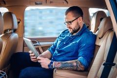 Um homem nos monóculos com tatuagem em seu braço usando o PC portátil da tabuleta em um banco traseiro de um carro Imagem de Stock