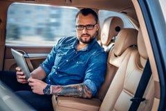 Um homem nos monóculos com tatuagem em seu braço usando o PC portátil da tabuleta em um banco traseiro de um carro Imagem de Stock Royalty Free