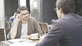 Um homem nos monóculos está escutando seu amigo no café fora Imagem de Stock