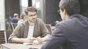 Um homem nos monóculos que fala a escuta seu amigo no café fora Fotos de Stock Royalty Free