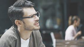 Um homem nos monóculos que fala no café fora Foto de Stock