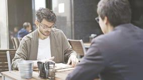 Um homem nos monóculos que olham em seus papéis no café fora Imagens de Stock