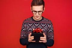 Um homem nos vidros com uma caixa de presente em suas mãos, olha-a, em um fundo vermelho imagens de stock