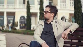 Um homem nos vidros em seus olhos senta-se em um banco e no descanso no ar fresco filme