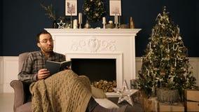 Um homem nos vidros na cadeira que lê um livro em casa no tempo do Natal para fora ruidosamente Interior do Natal vídeos de arquivo