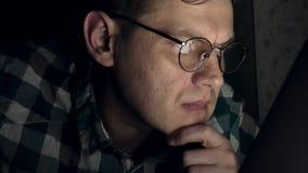 Um homem nos vidros trabalha tarde na noite Olha preocupado, ele vê no tela de computador na frente dele, um close-up filme