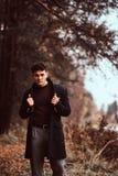 Um homem novo à moda considerável que levanta na floresta do outono fotos de stock royalty free