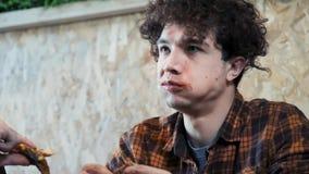 Um homem novo é feio e rudemente comendo sanduíches Come o fast food O conceito da sociedade da obesidade e da nutrição pobre vídeos de arquivo