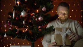 Um homem novo abre uma caixa de presente sob uma árvore de Natal vídeos de arquivo