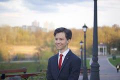 Um homem novo, um adolescente, em um terno clássico Passeio ao longo das avenidas do parque da mola imagem de stock