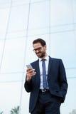 Um homem novo alto em um terno à moda lê a mensagem e o sorriso felizmente Fotos de Stock Royalty Free