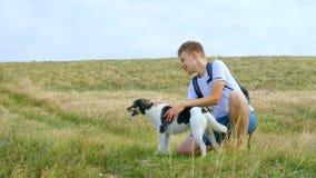Um homem novo anda com um cão ao longo da costa de mar filme