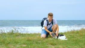 Um homem novo anda com um cão ao longo da costa de mar vídeos de arquivo