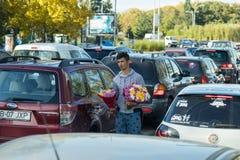 Um homem novo anda entre carros em uma estrada ocupada e vende flores na cidade de Bucareste em Romênia Foto de Stock