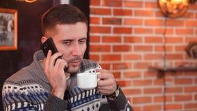 Um homem novo atrativo em um café bebendo do restaurante e fala em um telefone celular filme
