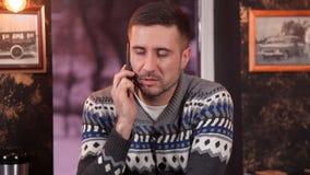 Um homem novo atrativo em um café bebendo do restaurante e fala em um telefone celular vídeos de arquivo