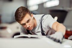 Um homem novo atrativo está lustrando um carro branco fotografia de stock royalty free
