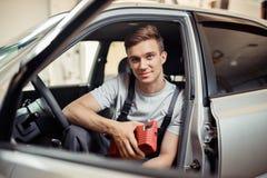 Um homem novo atrativo está sentando-se em um carro que está sendo reparado por ele foto de stock