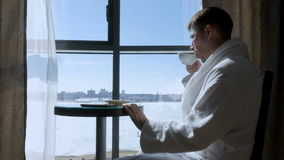 Um homem novo, atrativo que senta-se em uma tabela pelo chá bebendo da janela, café e escrevendo uma mensagem de SMS em um móbil Imagens de Stock