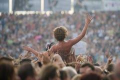 Um homem novo aumentou pela multidão durante um concerto Imagens de Stock Royalty Free