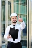 Um homem novo bonito com uma barba em uma camisa e um laço branco e um capacete branco da construção imagem de stock