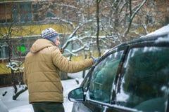 Um homem novo cancela a neve de um carro no inverno fotos de stock