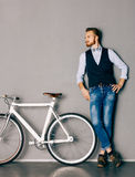 Um homem novo com bigode e barba está perto da bicicleta fixgear moderna elegante Calças de brim e camisa, veste e o styl do mode Imagens de Stock