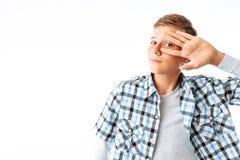 Um homem novo com um olhar pensativo, um indivíduo que guarda sua mão perto de sua cara, um menino com vidros no estúdio em um fu fotos de stock