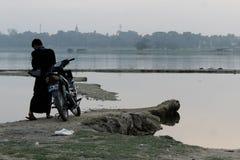 Um homem novo com seu 'trotinette' perto da ponte de U-Bein foto de stock royalty free