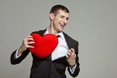 Um homem novo com um coração vermelho Fotos de Stock Royalty Free