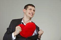 Um homem novo com um coração vermelho Fotografia de Stock Royalty Free
